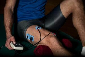 mand med elektroder på benet igang med at give sig selv elektroterapi